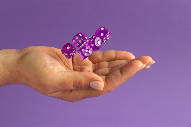 Hands holding dices on purple background