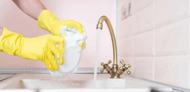 A hands holding dirty dish and wash it in the kitchen sink pouring water