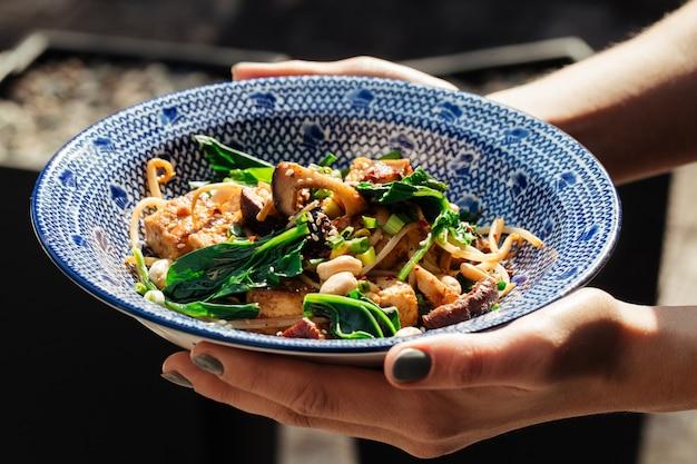 Руки держат блюдо из жареного тофу со шпинатом и орехами