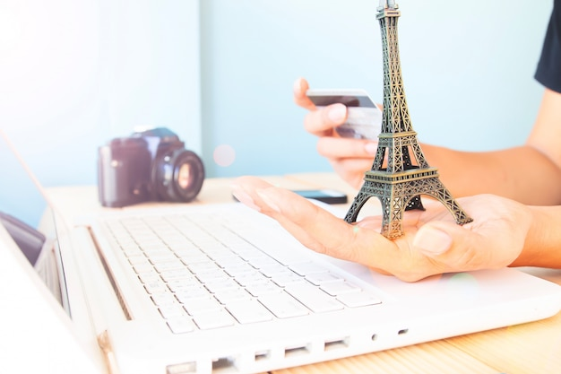 Hands holding eiffel tower model and credit card. woman using laptop computer and booking hotel.