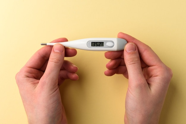 Hands holding a electronic thermometer with normal temperature on the display on yellow background.