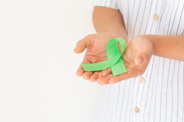Руки держат изумрудно-зеленую или нефритовую зеленую ленту на белом фоне с копией пространства, символ осведомленности о раке печени