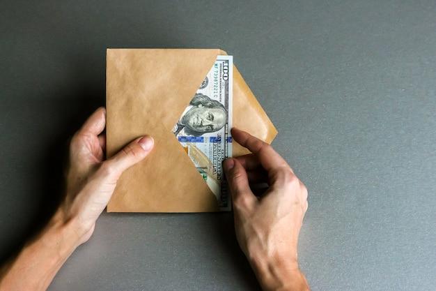 ドル紙幣の封筒を持っている手。