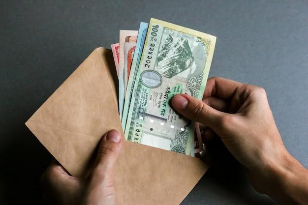 Руки держат конверт с непальской валютой (банкноты).