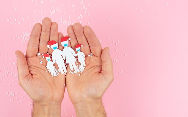 Hands holding a family cut out of paper with mask and christmas hat on a pink background.