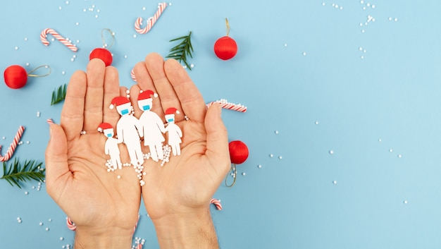 Hands holding a family cut out of paper with mask and christmas hat