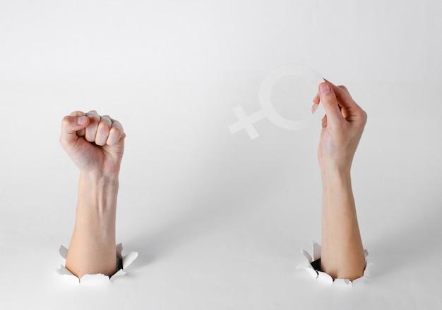女性の性別の記号を保持している手