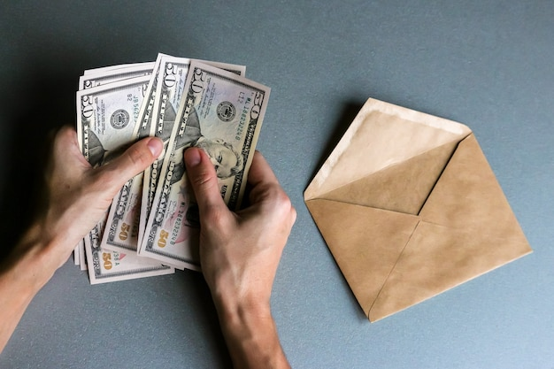 Hands holding fifty  dollar banknotes, envelope in background .