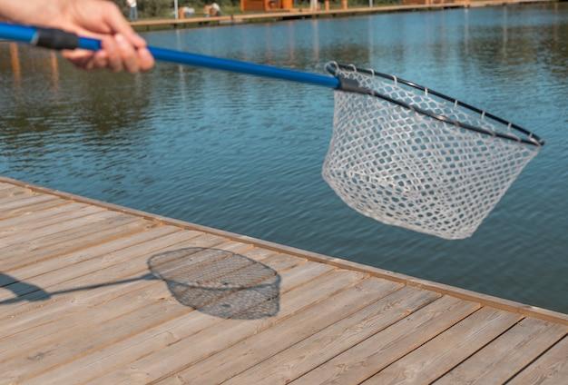 Руки держат рыболовную сеть с тенью на деревянной пристани