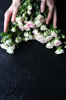 黒の背景に花を保持している手。バラの花束。花びらが付いた完璧なフラットレイ。幸せな母親の休日のはがき。国際女性の日の挨拶。広告やプロモーションのための誕生日のアイデア。