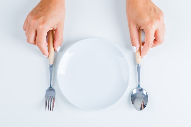 Hands holding fork and spoon