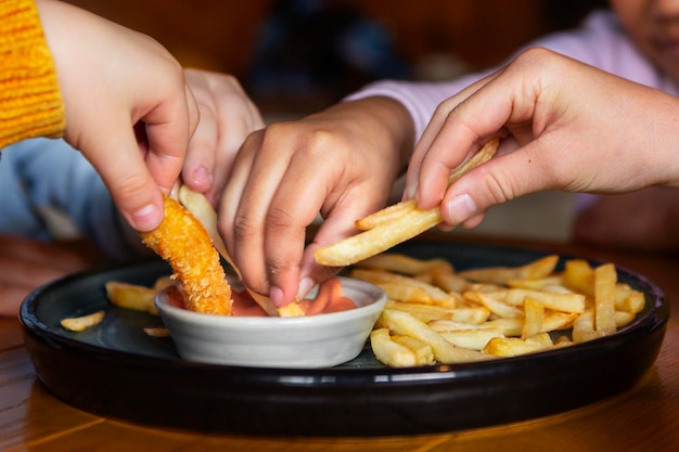 Hands holding french fries close up