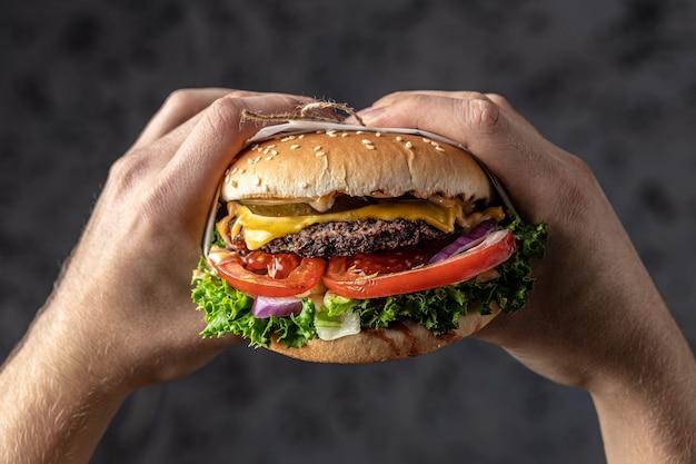 Руки держат свежий вкусный гамбургер, концепцию фаст-фуда и нездоровой пищи, баннер, меню, место рецепта для текста,
