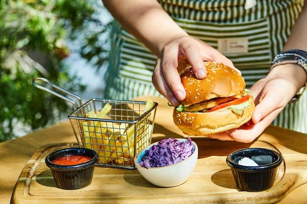 나무 테이블에 감자튀김과 소스를 곁들인 신선한 맛있는 버거를 손에 들고 있습니다.