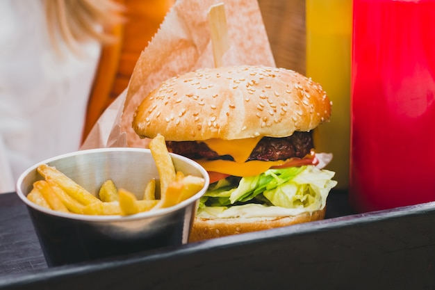 Hands holding fresh delicious burger with french fries on the black wooden table