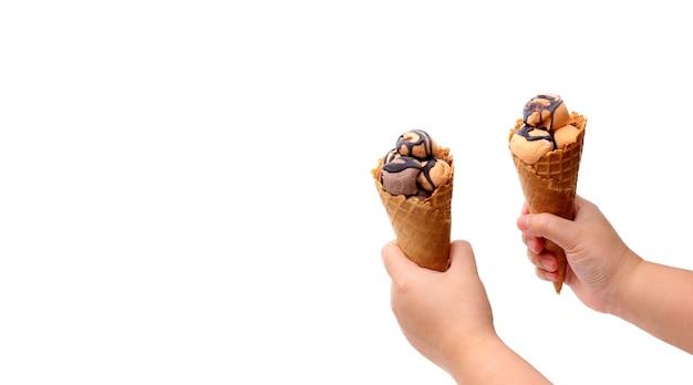 白い背景の上のアイスクリームの新鮮なワッフルコーンを保持している手。