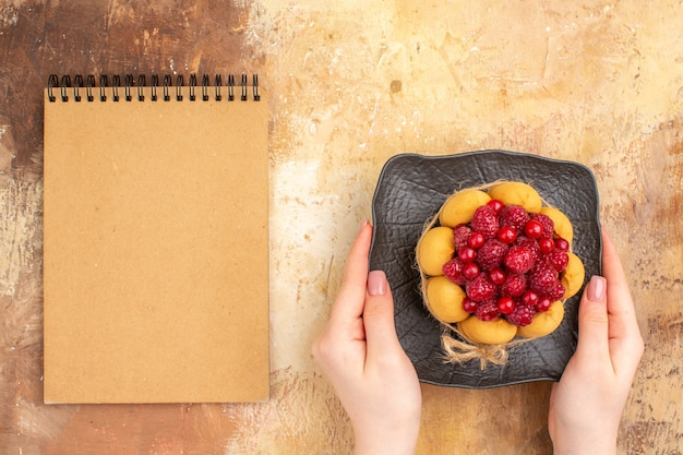 混合色のテーブルの茶色のプレートに焼きたてのギフトケーキとノートを持っている手
