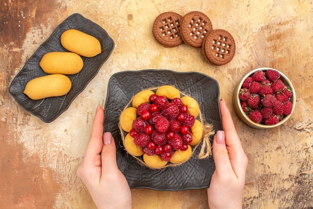 Hands holding freshly baked gift cake on a brown plate on mixed color table horizontal view