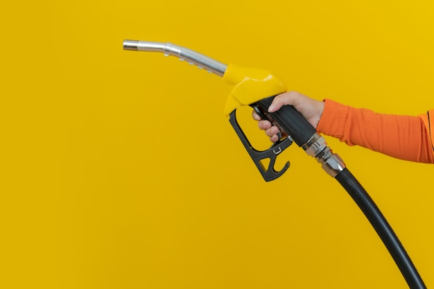 Hands holding fuel nozzle isolated on yellow background