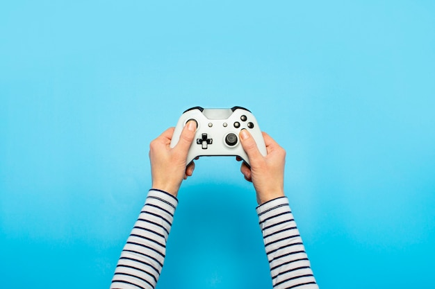 Hands holding a gamepad on a blue space. banner. concept games, video games
