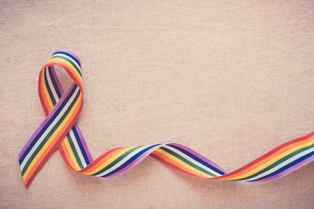 Hands holding gay pride rainbow ribbon for lgbt awareness