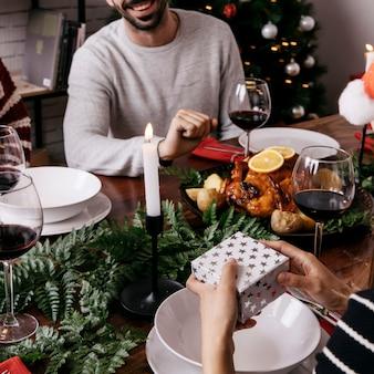 Руки с подарочной коробкой на рождественский ужин