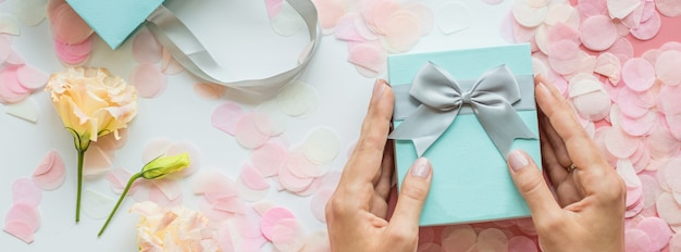 Hands holding gift box banner background