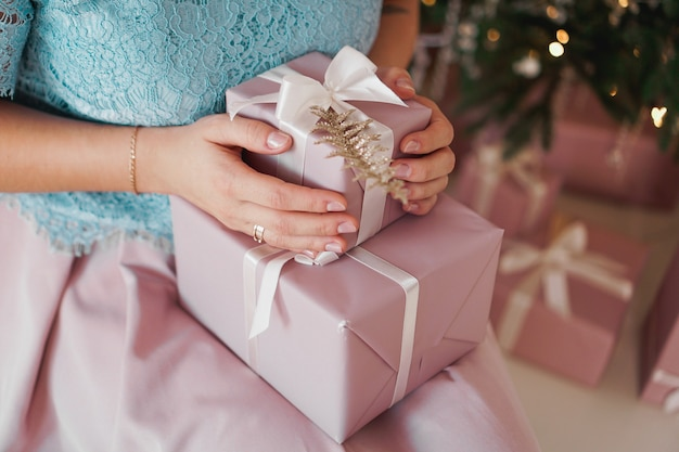 Hands holding gift present closeup of female hands giving the gift in the new year interior