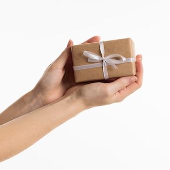 Mani che tengono il regalo con l'arco