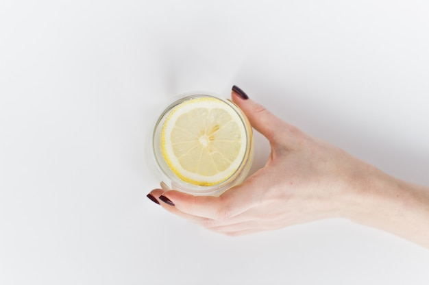 Hands holding a glass of clear water with lemon.