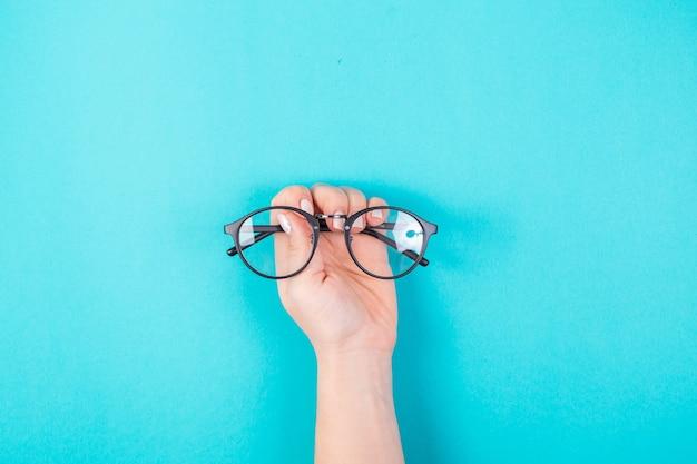 Руки держат очки на синем