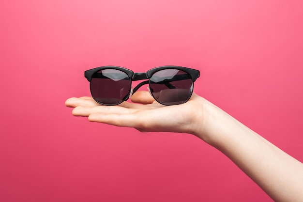 안경을 광고하는 분홍색 절연 된 벽에 안경을 들고 손