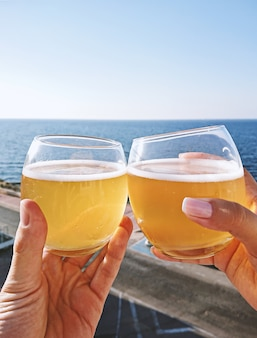 Hands holding glasses with cold beer against blue sky, closeup view