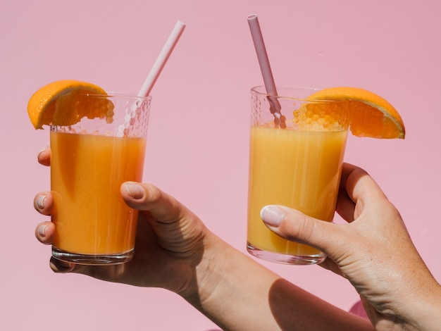 Hands holding glasses with natural orange juice front view