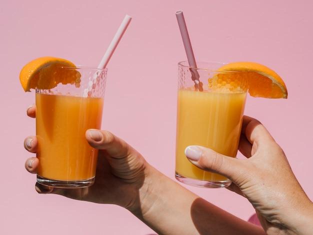 Руки держат очки с натуральным апельсиновым соком вид спереди