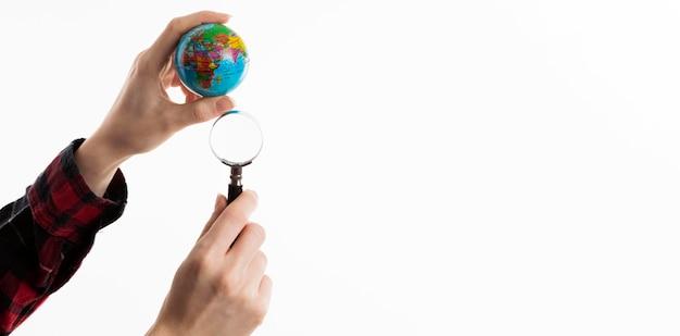 Mani che tengono globo e binocolo