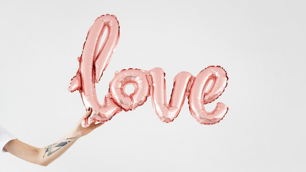 Hands holding a glossy pink love balloon