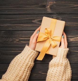 Руки держат золотую ленту связали подарок на рождество