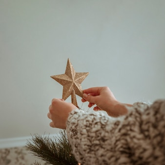 Hands holding golden top star for christmas tree