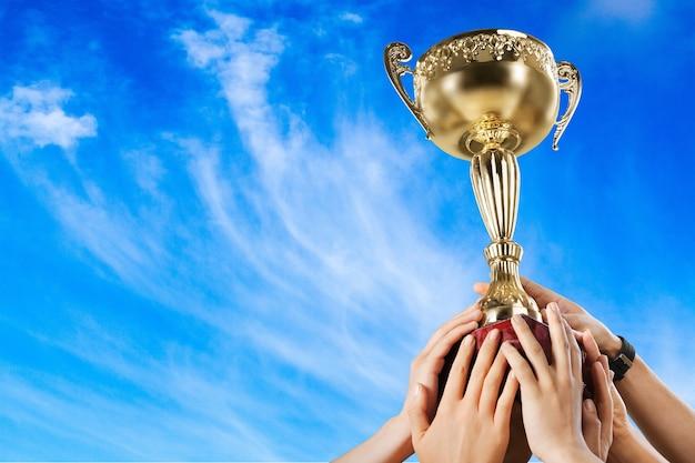 Руки, держащие золотой трофей на белом фоне