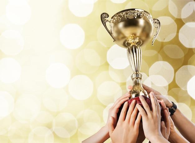 Руки держат золотой трофей на светлом фоне