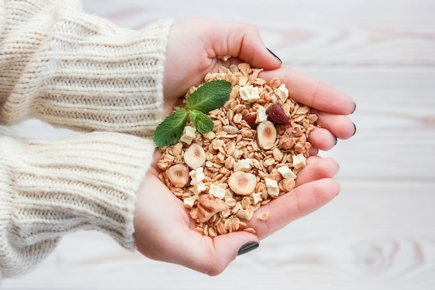 Hands holding granola with mint leaves