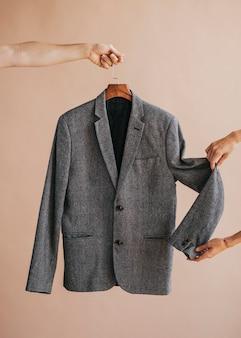 Hands holding a gray blazer in a hanger