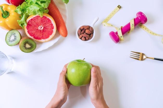 果物、野菜、ダンベル、テープメジャー、白いテーブルの上に水のガラスと青リンゴを保持している手。きれいな食事と運動で健康に良いコンセプトです。上面図。