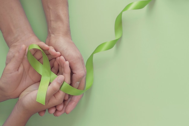 Hands holding green ribbon, world mental health day
