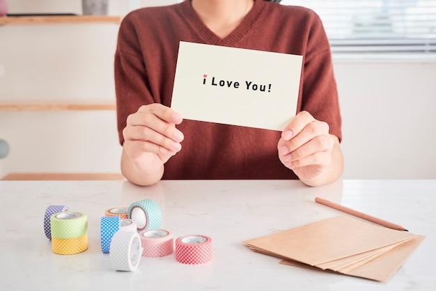 恋人のために用意された「愛してる」というフレーズの文字が入ったグリーティングカードを持つ手