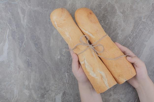 Mani che tengono un mezzo taglio di pane baguette francese sulla superficie in marmo