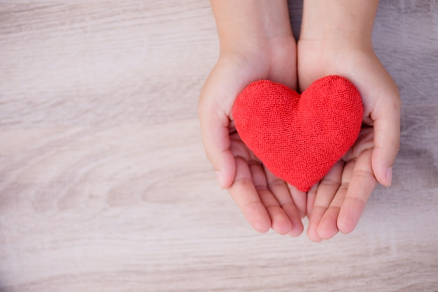 Hands holding handmade red heart on wooden background.