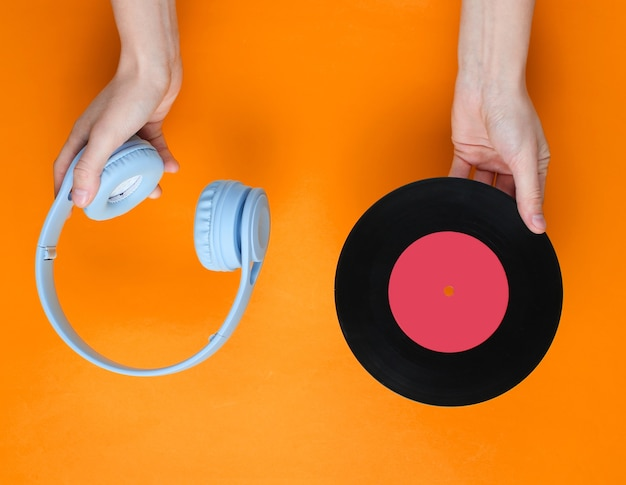 Hands holding headphones and vinyl record isolated