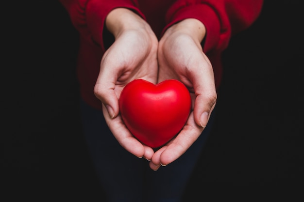 Hands holding a heart on a dark background